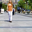 Beautiful red-haired girl in an orange shirt walks in the city — Stock Photo