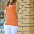 Beautiful red-haired caucasian girl in an orange shirt poses in front of a brick wall — Stock Photo #12561949