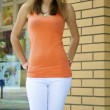 Beautiful red-haired caucasian girl in an orange shirt poses in front of a brick wall - 