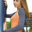Beautiful red-haired young girl in an orange shirt poses near a lamp post — Stock Photo