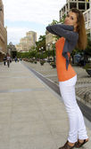Nice red hair girl poses in orange shirt on the city back ground — Stock Photo