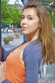 Beautiful red-haired young girl in an orange shirt poses near a lamp post — ストック写真