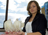 Cute Russian girl holds two white pigeons in her hands — Stock Photo