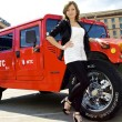 Stock Photo: Cute Russigirl poses near red hummer
