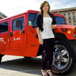 Cute girl poses near red hummer — Stock Photo