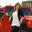 Cute girl poses near red hummer — Stock Photo #12585734