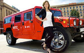 Cute Russian girl poses near red hummer — Stock Photo