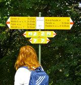Vrouw loopt in de buurt van het bord richting — Stockfoto