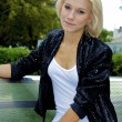 Beautiful blond caucasian model girl poses on the bench and watches on the — Stock Photo