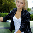 Beautiful blond caucasian model girl poses on the bench and watches on the — Stock Photo #12905850