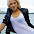 Beautiful blond caucasian model girl in black jacket and jeans shorts — Stock Photo #12908146