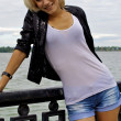 Beautiful blond caucasian model girl in black jacket and jeans shorts — Stock Photo
