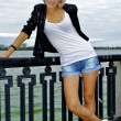Beautiful blond caucasian model girl in black jacket and jeans shorts — Stock Photo #12909632