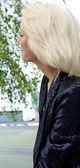 Schönes blond caucasian modell mädchen sitzt auf der bank und schaut nach vorn — Stockfoto
