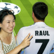 Chinese girl with the guy in Raul shirt - Stock Photo