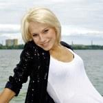 Nice blond caucasian model girl poses on the bridge and smiles — Stock Photo