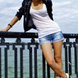 Beautiful blond caucasian model girl in black jacket and jeans shorts poses — Stock Photo