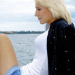 Beautiful blond caucasian model girl in black jacket and jeans shorts poses — Stock Photo #13157804