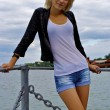 Stock Photo: Beautiful blond caucasian model girl in black jacket and jeans on the pier