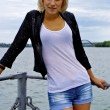 Beautiful blond caucasian model girl in black jacket and jeans on the pier — Stock Photo
