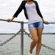 Beautiful blond caucasian model girl in black jacket and jeans on the pier — Stock Photo #13157851