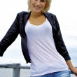 Beautiful blond caucasian model girl in black jacket and jeans on the pier — Stock Photo #13157855