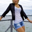 Beautiful blond caucasian model girl in black jacket and jeans on the pier — Stock Photo #13157859