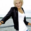 Beautiful blond caucasian model girl in black jacket and jeans on the pier — Stock Photo #13157861