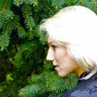 Beautiful blond caucasian model girl poses in front of green fir-tree — Stock Photo #13157978