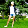 Beautiful blond caucasian model girl poses in front of green fir-tree — Stock Photo