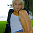 Beautiful blond caucasian model girl back in black jacket and jeans sits on — Stock Photo