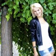 Beautiful blond caucasian model girl poses near the green tree as a backgo — Stock Photo