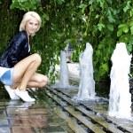 Beautiful blond caucasian model girl iposes near small fountain — Stock Photo #13158487