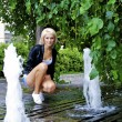 Beautiful blond caucasian model girl poses near small fountain — Stock Photo #13158507