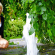Beautiful blond caucasian model girl poses near small fountain — Stock Photo