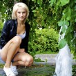 Beautiful blond caucasian model girl poses near small fountain — Stock Photo #13158537