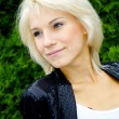 Portrait of a beautiful blond caucasian model girl poses near the green — Stock Photo #13158596