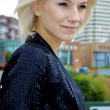Beautiful blond smiling caucasian model girl in front of the city — Stock Photo #13158779