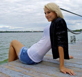 Nice blond caucasian model girl poses on the pier — Stock Photo
