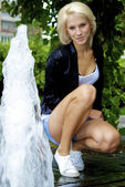 Beautiful blond caucasian model girl iposes near small fountain — Stock Photo