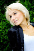 Portrait of a beautiful blond caucasian model girl poses near the green — Stock Photo