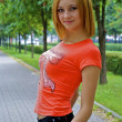 Beautiful sexual young girl in an orange shirt poses on the alley — Stock Photo #13260346