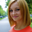 Portrait of a beautiful sexual young blond girl in an orange shirt poses on — Stock Photo