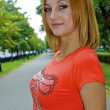 Beautiful sexual young blond girl in an orange shirt poses on the alley — Stock Photo #13260366
