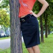 Beautiful sexual young blond girl in an orange shirt near the tree — Stock Photo #13260393