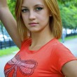 Beautiful sexual young blond girl in an orange shirt near the tree — Stock Photo #13260398