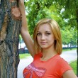 Beautiful sexual young blond girl in an orange shirt near the tree — Stock Photo #13260401