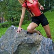Beautiful sexual girl poses near the stone wearing red and black — Stock Photo #13260897