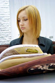 Beautiful blond girl reads very huge menu — Stock Photo