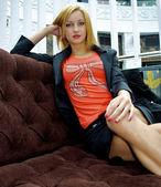 Bella ragazza vestita bene pose sul divano — Foto Stock